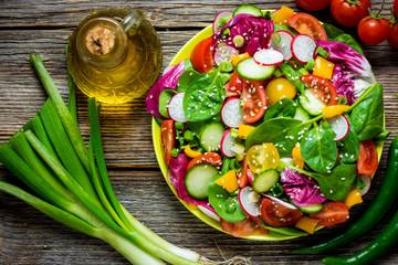 FototapetaFresh vegetable salad on wooden background