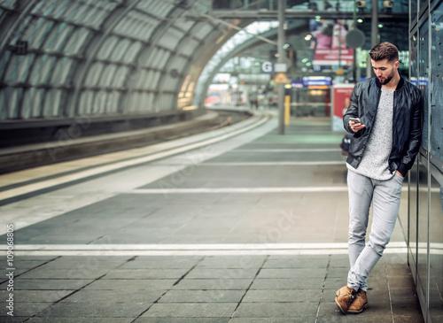 Zdjęcie XXL Młody człowiek z smartphone w staci kolejowej