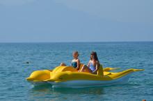 Girls On Yellow Pedalo Paddle Boat In The Mediterranean Sea, Kusadasi, Turkish Riviera, Turkey