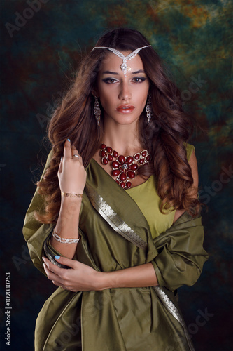 Poster Gypsy Beautiful woman in green indian sari and jewelry on colorful bac