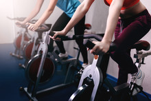 Woman On Fitness Exercise Bike...
