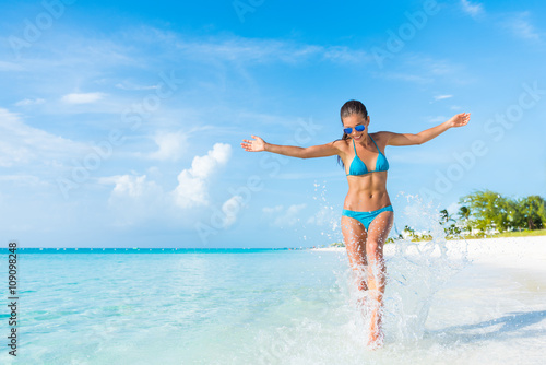 Fototapeta Freedom carefree girl playing splashing water having fun on tropical beach vacation getaway travel holiday destination. Playful woman with abs slim bikini body relaxing feeling free. obraz na płótnie