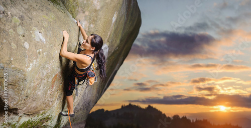 Young attractive female rock climber climbing challenging route on steep rock wall against scenic sunset background. Summer time. Climbing equipment