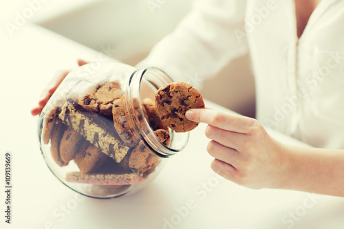 Fotografia close up of hands with chocolate cookies in jar