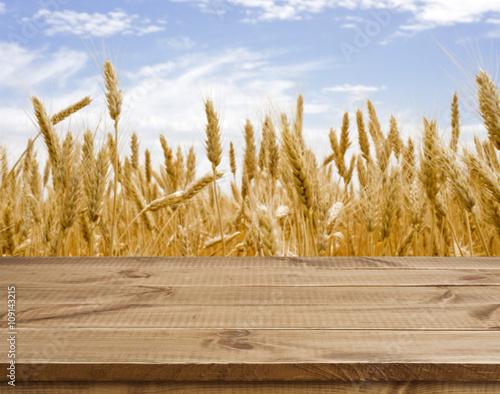 Fotobehang Zwavel geel Wooden table surface over defocused golden wheat field landscape background
