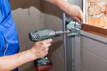 Garage Doors Installation.Worker Installing  Lifting System In Metal Profil With Screwdriver