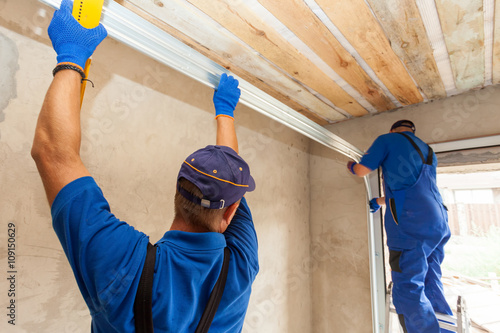 Garage doors installation. Workers installing Post Rail and Spring Installation / Assembly.