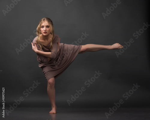 Contemporary dance. Beautiful elegant woman dances on gray background