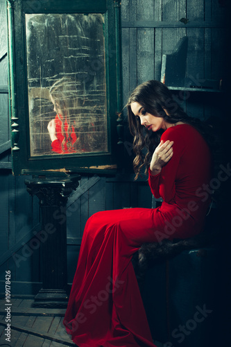 Fotografie, Obraz  Woman in red dress near mirror