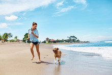 Beautiful Happy Woman Running With Her Dog, Golden Retriever On Wet Sand On The Beach By Sea. Girl Enjoying Summer Holidays Vacations, Having Fun With Her Pet. Summertime Concept.
