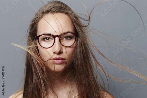 Valokuva  Beautiful brunette in spectacles with windswept hair