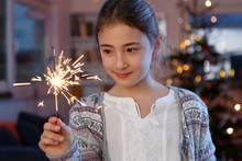 Girls In Front Of Christmas Tree Holding Sparkler Looking Down Smiling