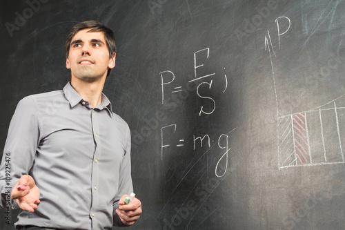 Fotografie, Tablou  Portrait of young happy smiling teacher man standing near chalkboard with mathem