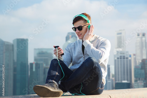 Photo  happy young man in headphones with smartphone
