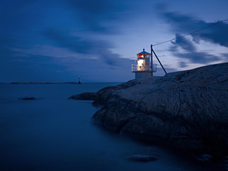 Lighthouse on rocky coast at dusk