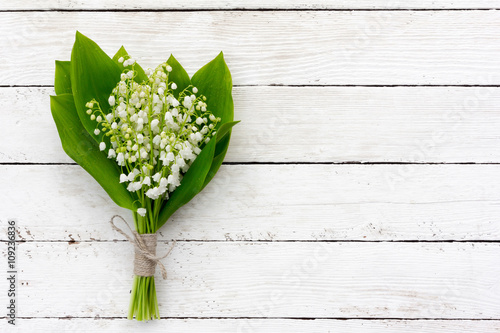 Muguet de mai bouquet of lilies of the valley flowers with green leaves tied with twine in the water droplets on the white wooden boards. with space for posting information