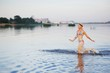 Girl runs into water in swimsuit. Beauty Model Girl Splashing Water with her legs. Beautiful Woman in Water