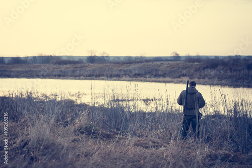 Foto op Canvas Jacht Hunter man standing at river bank in expectation of successful hunting during misty sunrise in rural field and watching on beautiful sunrise with copy space