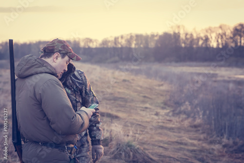 Foto op Aluminium Jacht Hunters in rural field during hunting season holding smartphone and checking their location via GPS