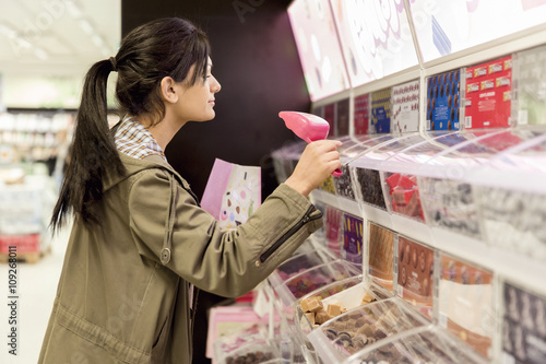 Woman choosing sweets in shop