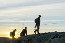 Men With Fishing Rods Walking On Coast