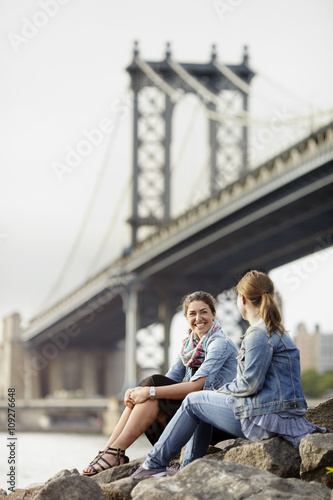 Two female tourists sitting on rock by river with Brooklyn Bridge in background