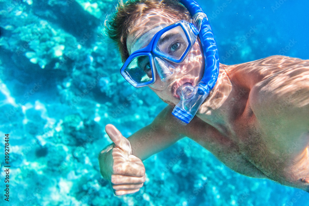 Fototapeta Snorkeling man underwater giving thumbs up ok signal wearing snorkel and mask having fun on beach summer holidays vacation enjoying recreational leisure time swimming in the sea.