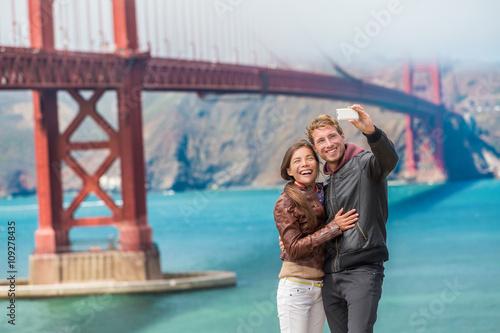 Plakat Szczęśliwi potomstwa dobierają się turystów bierze selfie w San Fransisco Golden Gate Bridge. Międzyrasowa młoda nowożytna para używa mądrze telefon. Azjatycka kobieta, Kaukaski mężczyzna.