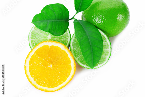 Slices of fresh orange with lime and leaf on white background