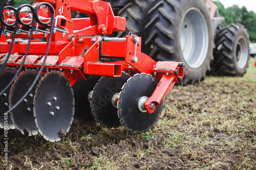 Foto  Plow modern tech red tractor close up on an agricultural field Mechanism