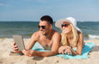 happy couple with tablet pc sunbathing on beach
