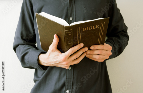 Photo  Man, priest or believer, is holding and reading open Holy Bible, main religious