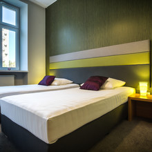 Two Neat, Single Beds In Green Hotel Room