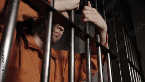 Photo Caucasian Prisoner behind bars in Jail - Criminal Justice system