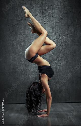 Photo Beautiful sexy young woman working out , doing yoga exercise , handstand