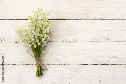 Photo Stands Lily of the valley lily of the valley bouquet of white flowers tied with string on a white background barn boards. with space for posting information