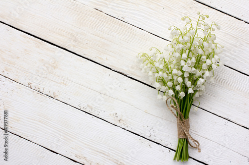 Poster Muguet de mai lily of the valley bouquet of white flowers tied with string on a white background barn boards. with space for posting information