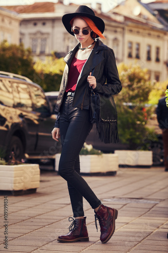 2d36879ecc8 Outdoor full body portrait of young beautiful fashionable lady walking on  the street. Model wearing wide-brimmed hat and stylish leather clothes.  Girl .