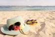 Summer vacation concept with straw hat, sunglasses and flip flops on sandy tropical beach - vintage color styles