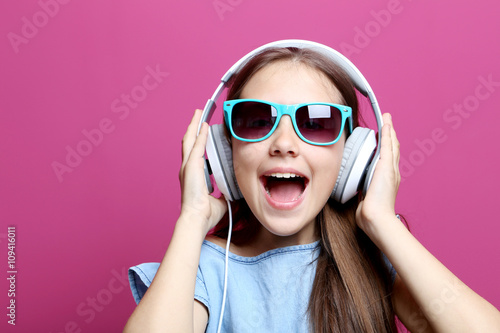 Poster Magasin de musique Portrait of young girl with headphones on pink background
