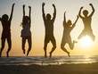 group of people jumping at beach. Backlight shot.