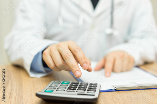 Photo doctor is calculating cost of treatment