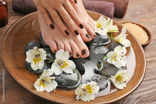 Foto op Plexiglas Manicured female feet and hands in spa wooden bowl with flowers and water closeup
