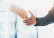 Business partnership meeting photo. Image businessmans handshake. Successful businessmen handshaking after good deal. Horizontal, blurred background