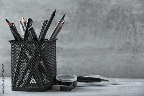 Fotografie, Obraz  Pens and pencils in metal holder in front of wall background
