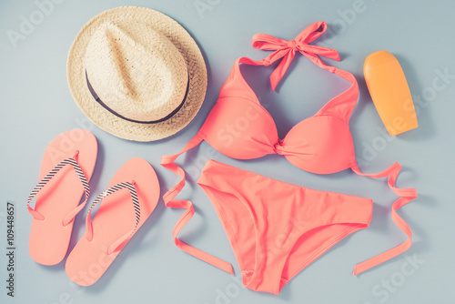 Fotografie, Obraz  Pink swimsuit with beach accessories on blue background