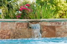Luxurious Swimming Pool With Stone Waterfall And Pink Roses In B