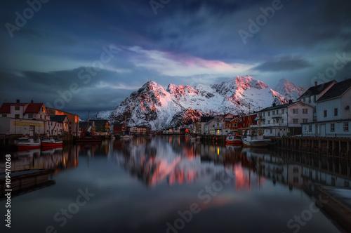 Foto auf Gartenposter Nordlicht Henningsvaer village reflections with mountains in red sunrise light, Lofoten