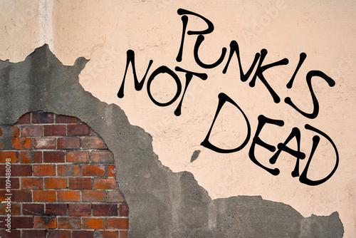 Foto op Aluminium Graffiti Handwritten graffiti Punk Is Not Dead sprayed on the wall, anarchist aesthetics. Appeal to alternative subculture