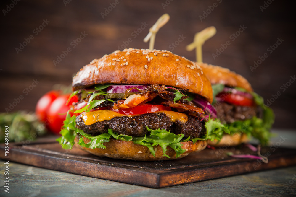 Fototapety, obrazy: Tasty burgers on wooden table.